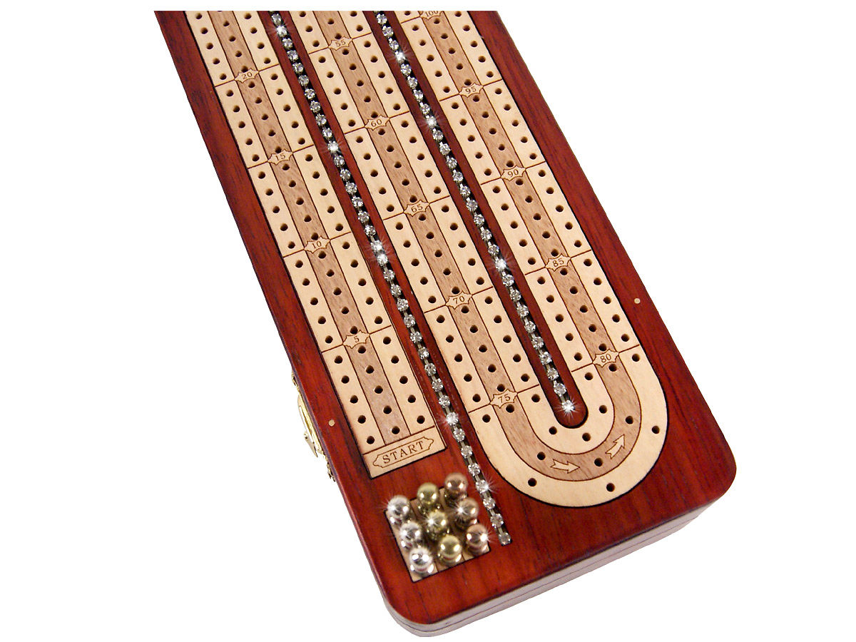Close up view of cribbage board with crystals inlaid in between tracks